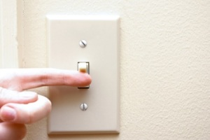 a-hand-turning-on-a-light-switch